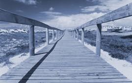 A long wooden boardwalk across a beach landscape