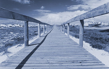 A long wooden boardwalk across a beach landscape