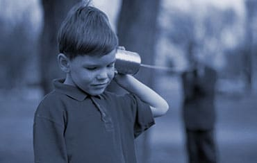 Two boys using a tin can telephone